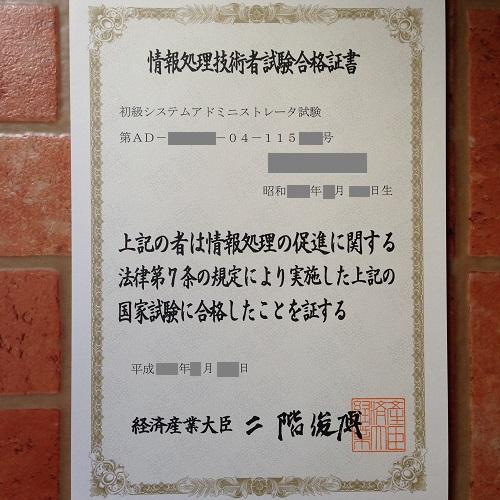 初級システムアドミニストレーターの合格証書を正面から撮影した写真。賞状に似て金の縁取りがあり、文面や大臣の署名は毛筆で記載されている。