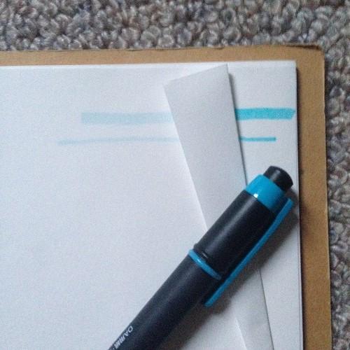 クロッキー帳の白紙を、正面から撮影した写真。白紙には水色の蛍光ペンで線が引かれている。