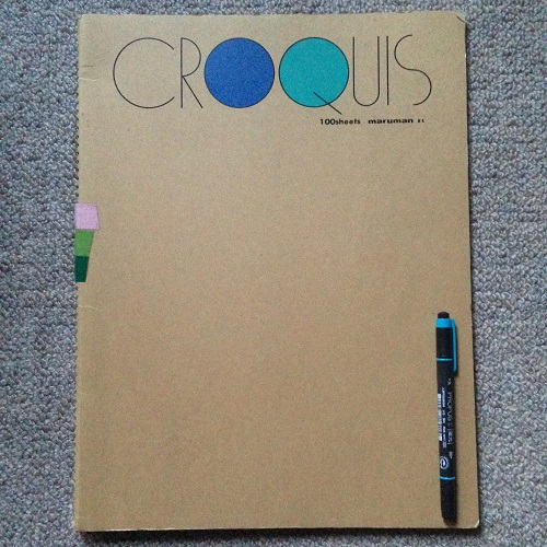 市販のクロッキー帳と蛍光ペンとを並べ、大きさを比較している写真。蛍光ペンは水色。