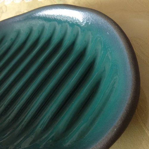 電子レンジで魚が焼けるふしぎなお皿(小判型)に近づいて撮影した写真。青緑色の皿に溝が何本もついている。