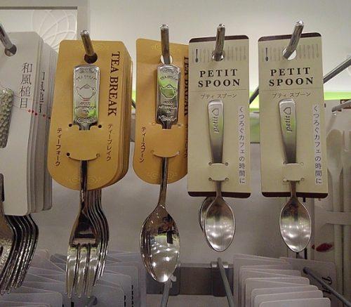 Seriaで販売されていた10cm以下のミニスプーンを正面から撮影した写真。ミニスプーンのパッケージには「Petit Spoon」と製品名がついている。画面左に柄の長いスプーンやフォークも映り込んでいる。