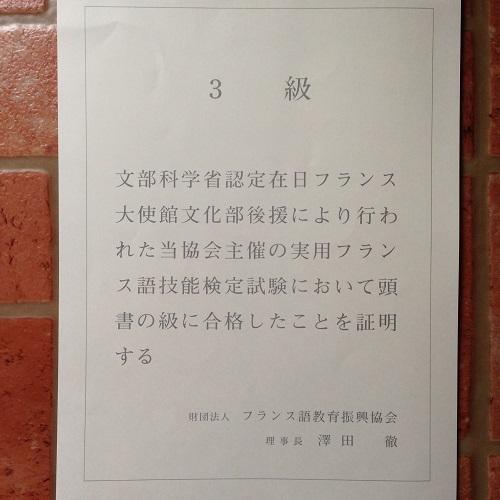 実用フランス語検定3級の合格証書を裏返し、レンガの床に置いて撮影した写真。白い賞状に、全文が日本語で書かれている。