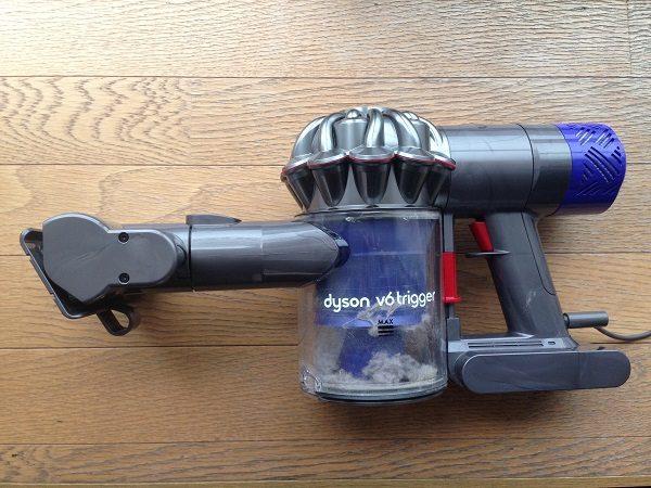 布団掃除機Dyson V6 Triggerの全体像を真横から撮影した写真。布団掃除機は灰色で所々に濃い青が配置されているデザインで、人が操作するボタンなどは赤色になっている。中央に透明なプラスチックでできた出すとボックスがあり、埃が少し溜まっている