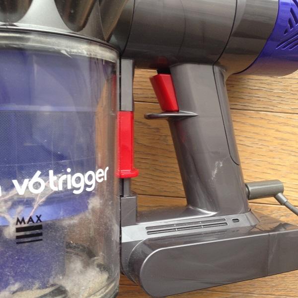 布団掃除機Dyson V6 Triggerの持ち手の部分を拡大して撮影した写真。電源オンオフを切り替える赤いボタンと「v6 trigger」と書かれた白いロゴが見えている