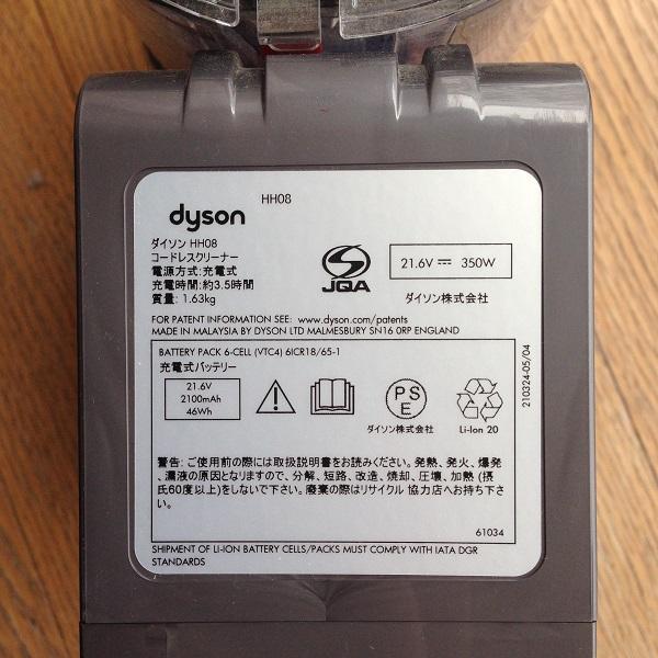 布団掃除機Dyson V6 Triggerの底面を撮影した写真。底面に、重さや充電時間や使用上の注意などが明記されているシールが貼られている。