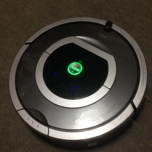自動掃除機ルンバを手前からカメラで撮影した写真。ルンバのボディは薄灰色と濃灰色で、ルンバの中央に「CLEAN」と書かれたボタンがあり、緑色に光っている。ルンバは灰色のカーペットの上に置かれており、ボディは引っ掻いたような小さな傷が無数についている。