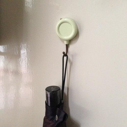 黒い男性用折り畳み傘を、白っぽいマグネットフックに吊るし、白い扉に貼り付けて保管している写真。