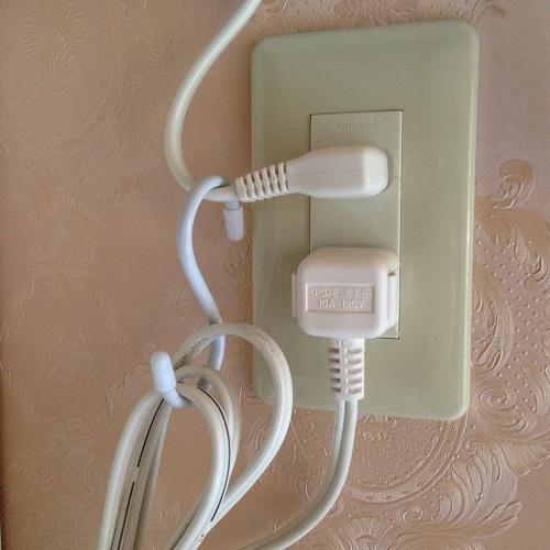 電源コンセントから伸びている電源ケーブルを、軽く束ねてS字フックで吊るしている写真。