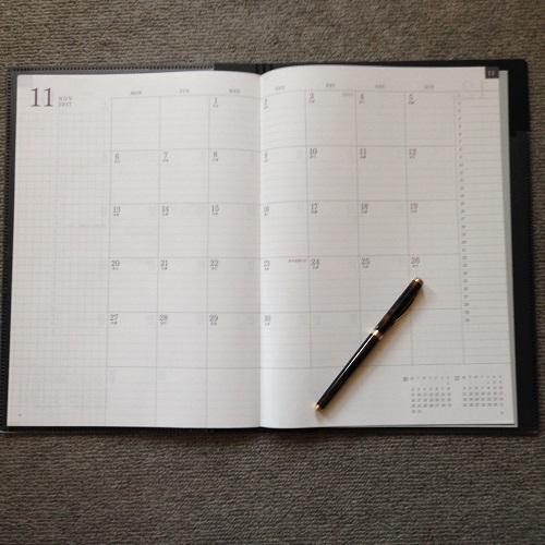 「ミドリ フラットダイアリー マンスリー手帳」(A4サイズ)を開き、正面から全体像を撮影した写真。11月のページが見開きで写っている。左ページの左側に罫線の引かれたメモ欄があり、中央に1日1マスのマンスリー欄が写っている。背景は灰色カーペット。