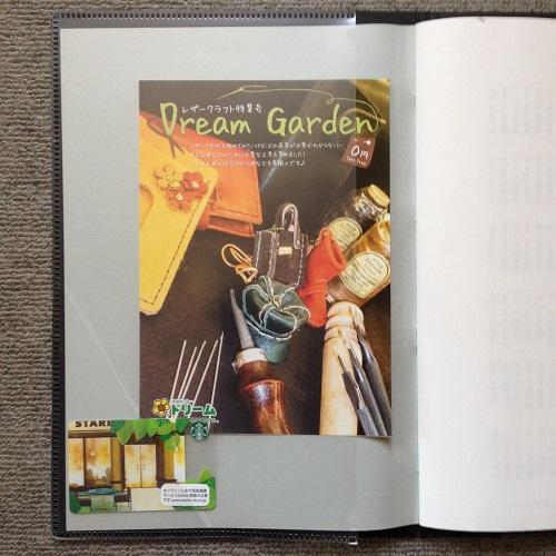 「ミドリ フラットダイアリー マンスリー手帳」(A4サイズ)の手帳カバー表表紙の裏を、正面から撮影した写真。透明な大きなポケットが1つ写っている。ポケットの下部に切れ込みが入っており、スターバックスのカードが挟まっている。