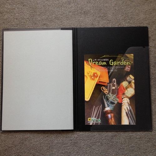 「ミドリ フラットダイアリー マンスリー手帳」(A4サイズ)の手帳カバー裏表紙の裏側を、正面から撮影した写真。裏表紙は黒色。ポケットは透明で、右上から左下にかけて口が開いており、A5サイズのチラシが1枚入れられている。向かって左側には手帳のリフィルが入っている。