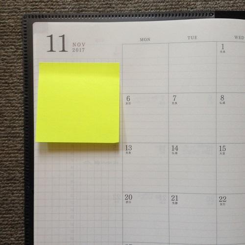 「ミドリ フラットダイアリー マンスリー手帳」(A4サイズ)のページに正方形のポストイットを貼り、正面から撮影した写真。付箋紙はあざやかな黄色で、文字は何も書かれていない。