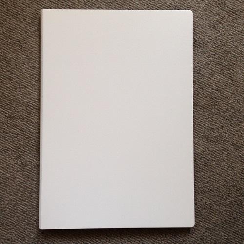 「ミドリ フラットダイアリー マンスリー手帳」(A4サイズ)の手帳カバーを正面から撮影した写真。カバーはプラスチックのような材質でできており、色は白。カバーに汚れやシミは見受けられない。
