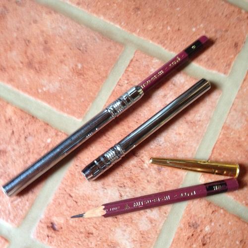 三菱鉛筆3本と金属製の鉛筆ホルダー2つと鉛筆キャップを撮影した写真。