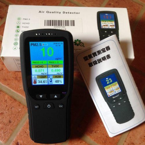 空気質測定器を正面から撮影した写真。取扱説明書とパッケージ(白い箱)も写っている。