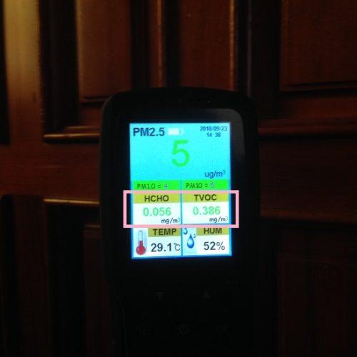 木製扉の前で空気環境測定を行っている写真。扉は1ヶ月前にBRIWAXが塗布されたもの。TVOCの値は0.386mg/㎡と表示されている。