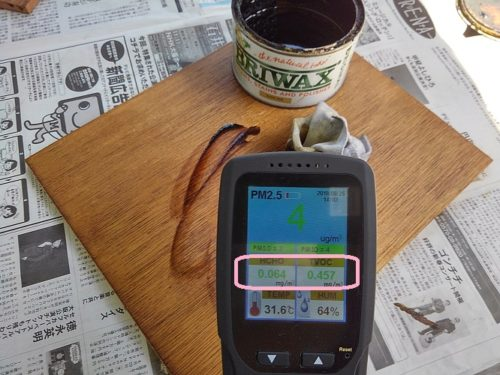 BRIWAX塗布中に空気質測定器を正面から撮影した写真。HCHOが0.064mg、TVOCが0.457mg、PM2.5が4μgと表示されている。背景にはBRIWAX塗布中の木の板とBRIWAXの缶と新聞紙が写り込んでいる。