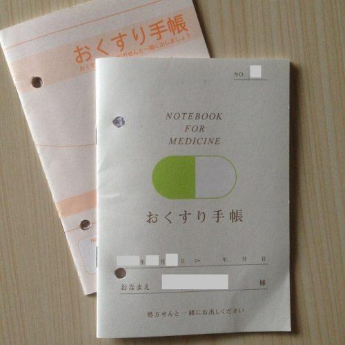 おくすり手帳2冊を正面から撮影した写真。うち1冊には錠剤のイラストが描かれている。