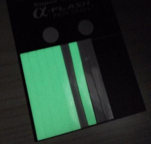 暗闇の中で超高輝度蓄光テープが「Super α-FLASH」が緑色の光を発している写真。蓄光テープは長方形型で、光も緑の長方形のように見える。