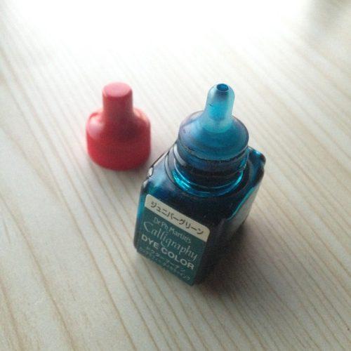 ドクターマーチンカリグラフィーダイカラー「ジュニバーグリーン」の蓋を開いたところを撮影した写真。インクボトルが目薬の容器に似ている。