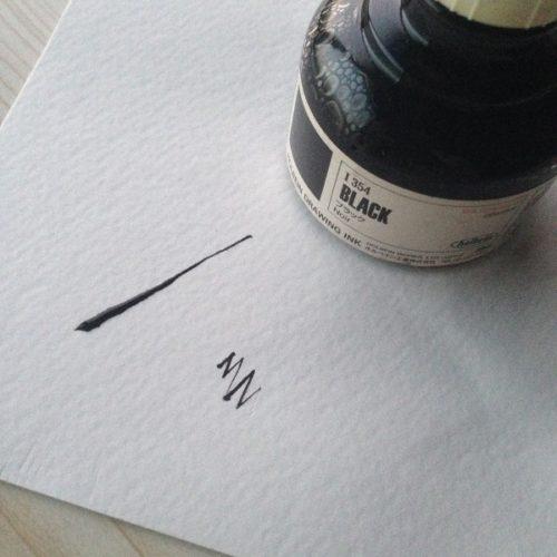 ホルベイン社のドローイングインク「BLACK」を撮影した写真。インクの手前に白い紙が置かれており、黒いインクで描かれた線が写っている。