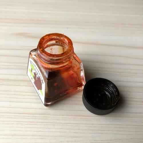 「ウィンザー&ニュートン」カラーインクの瓶の蓋を開いて撮影した写真。残り少ないバーントシエンナがインク瓶の底に残っている。