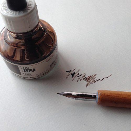 ホルベイン社のドローイングインク「SEPIA」を斜め上から撮影した写真。インクの手前につけペンが写り込んでいる。