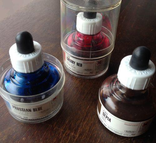 ホルベイン社のドローイングインクを撮影した写真。「チェリーレッド」「プルシャンブルー」「セピア」のインクが写っている。