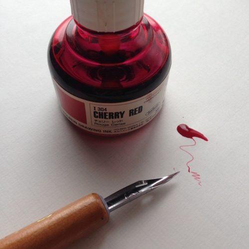 ホルベインドローイングインク「チェリーレッド」を正面から撮影した写真。インク瓶の手前にインクが少量こぼれている。