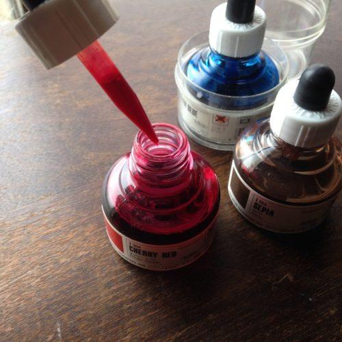 ホルベインドローイングインク「チェリーレッド」の蓋を開いたところを撮影した写真。ボトルの蓋についたスポイトが、正面に写っている。