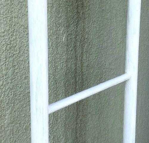 白い水性錆び止めを塗ったばかりのハシゴを、はしごに近づいて撮影した写真。ハシゴの表面に、うっすらと塗り跡が見えている。ハシゴの背景は薄緑色の壁。