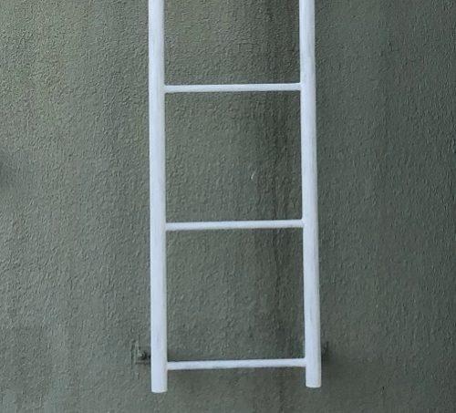 白いペンキが塗られたばかりの梯子を正面から撮影した写真。梯子の後ろに薄緑色の汚れた壁が映っている。