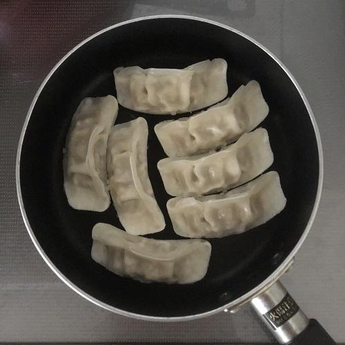 味の素の冷凍餃子を黒いフライパンに並べた様子を真上から撮影した写真。小型のフライパンに餃子が7つ入っている。