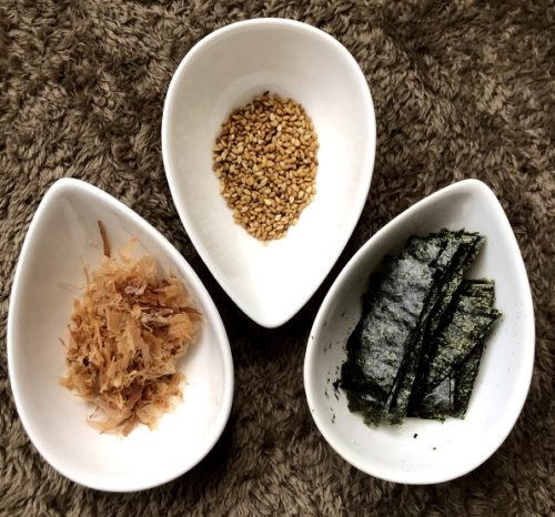 うどんの薬味を白い皿に入れ、真上から撮影した写真。右から順に海苔、胡麻、かつおぶしが写っている。